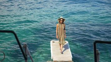 A woman traveling alone on a dock over the Mediterranean Sea in Italy, Europe. video