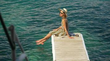 A woman with a glass of white wine on a dock over the Mediterranean Sea in Italy, Europe. video