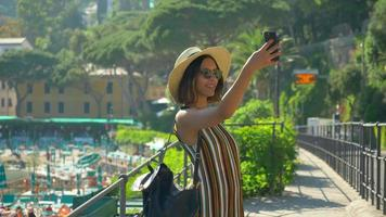 A woman takes selfies and uses facetime video calling in a luxury resort town in Italy, Europe.
