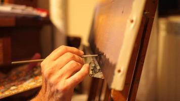 close-up da mão e do pincel de um artista enquanto ele pinta uma pintura a óleo sobre tela dentro de seu estúdio de arte. video