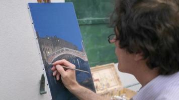 um artista pinta uma pintura a óleo na tela externa. video