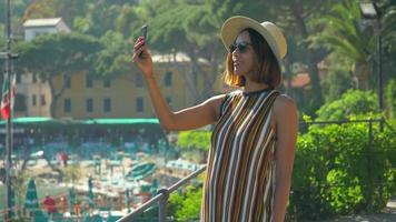 A woman takes pictures with her mobile device phone at a beach resort in a luxury resort town in Italy, Europe. video
