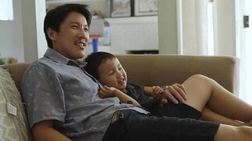 padre, abrazar, hijo joven, en, sofá, en casa foto