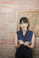 Attractive business woman smiling on brick wall photo