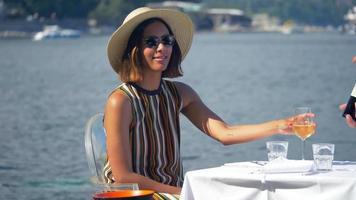 uma mulher com uma taça de vinho branco em um restaurante com vista para o mar mediterrâneo na itália, europa. video