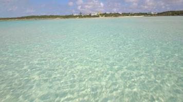 Aerial drone view of clear water and houses on a tropical island beach and coast in the Bahamas, Caribbean. video
