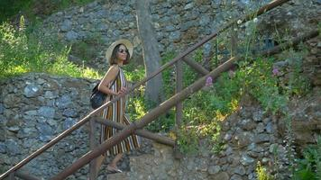 A woman walks up stairs at a Mediterranean Sea beach club in a luxury resort town in Italy, Europe. video