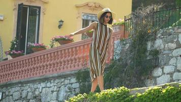 A woman walking near a beach club in a luxury resort town in Italy, Europe. video