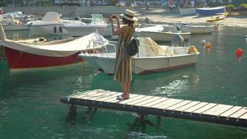 uma mulher em uma doca em portofino, itália, um resort de luxo na europa. video