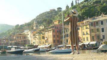 una mujer que toma fotografías con su teléfono móvil mientras viaja en portofino, italia. video