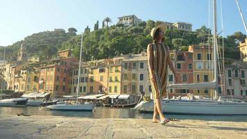 uma mulher andando com um chapéu e uma bolsa de mochila viajando em portofino, itália, um resort de luxo na europa. video