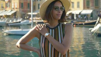 A woman with a watch, hat, sunglasses, striped dress traveling in Portofino, Italy, a luxury resort town in Europe. video
