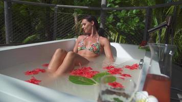 en kvinna i ett spa-badkar med en blomma i håret. video