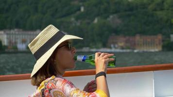 A woman traveling with hat drinks beer on ferry on Lake Como, Italy, Europe. video