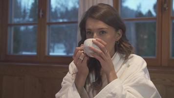 A woman drinking tea in a hotel room at a ski resort. video