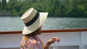 A woman traveling with hat drinks bottled water on ferry on Lake Como, Italy, Europe. video