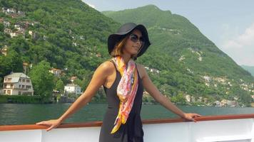 A woman wears a hat while traveling to a luxury resort town on a ferry near Lake Como, Italy, Europe. video