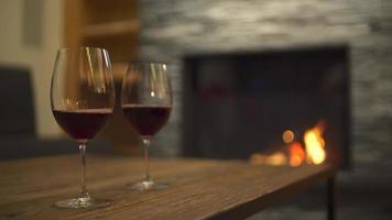vino rosso che si versa in bicchieri e un caminetto in un ristorante in un resort di lusso. video