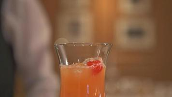 A bartender mixes a drink and puts a cherry on top. video