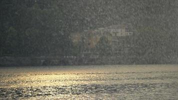 soleil et pluie pleuvant un jour de tempête sur le lac de côme, italie, europe. video