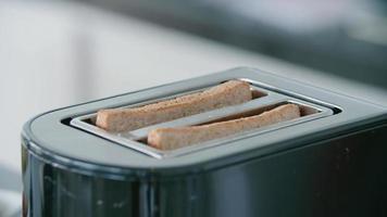 le pain est grillé comme du pain grillé dans un grille-pain pour le petit déjeuner. video