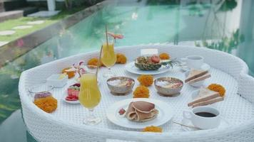 A breakfast tray is prepared and floated in a pool at a resort hotel. video