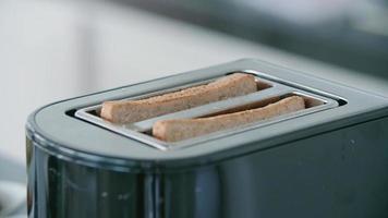 il pane viene tostato come toast in un tostapane per colazione. video