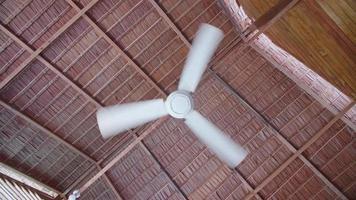 ventilateur de plafond refroidissant dans un complexe hôtelier au toit de chaume d'une île tropicale. video