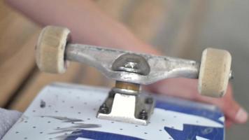 un joven trabaja para arreglar su patineta con una herramienta. video
