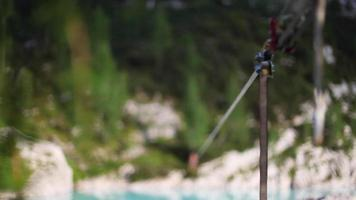 A man tries to balance while slacklining on a tightrope and walking over a lake. video