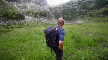 un hombre de excursión y mochilero por un sendero en las montañas. video