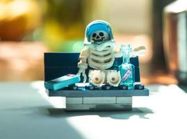 Warsaw, Poland, May 2019 - Lego mini-figure skeleton sitting on the bench photo
