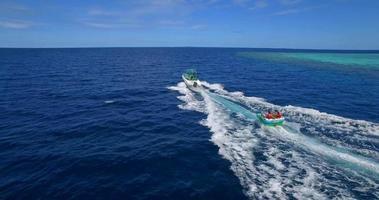vista aerea del drone di un uomo e una donna su un tubo gonfiabile che rimorchia dietro una barca verso un'isola tropicale. video