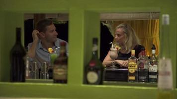 Ein Mann und eine Frau trinken einen Drink in einer Bar eines Resorts. video