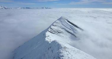 Vista aérea de drones por encima de las nubes y montañas cubiertas de nieve en el invierno. video
