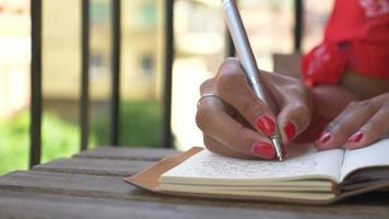 Close-up of a woman writing in a journal diary traveling in a luxury resort town in Italy, Europe. video