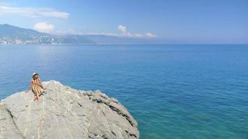 A woman on rocks with a cruise ship traveling in a luxury resort town in Italy, Europe. video