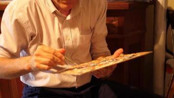 um artista pinta uma pintura a óleo sobre tela dentro de seu estúdio de arte. video