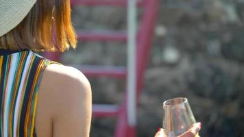 A woman with a glass of white wine on a ladder in a luxury resort town in Italy, Europe. video