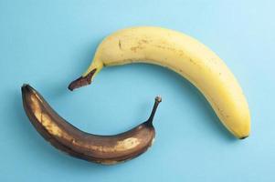 Concepto de flatlay mínimo hecho de plátanos maduros y podridos sobre fondo azul. foto