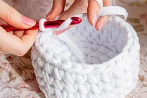 Young woman while crocheting, close up. photo