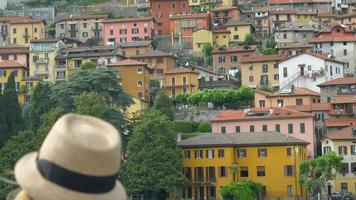 A woman wearing a fedora hat looking at an Italian village on Lake Como, Italy, Europe. video