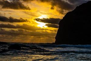 Sunsetting and waves rushing on the beach. Bethels Beach, Auckland, New Zealand photo