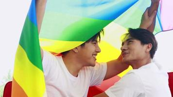 Gay couple holding a rainbow flag in at home with smiling faces happy Concept LGBT of homosexual love and life video
