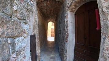 lumière au bout du tunnel, pov de marcher sur un chemin étroit dans le village de pienza, toscane, italie, europe. video