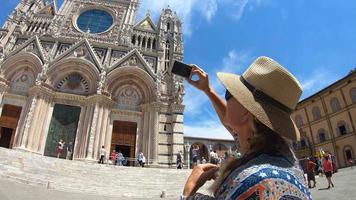 Una mujer tomando fotografías con una cámara de teléfono de dispositivo móvil de la catedral duomo di siena en el pueblo de siena, toscana, italia, europa. video