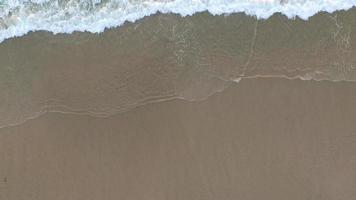 plan aérien de vagues se brisant sur la plage. video