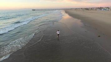 prise de vue aérienne d'un jeune homme qui court sur la plage. video