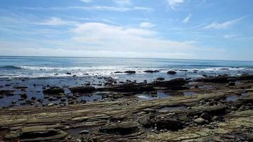 una pintoresca costa de playa rocosa. video