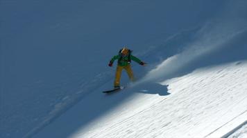 un snowboarder haciendo snowboard en montañas cubiertas de nieve. video